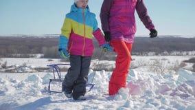 Счастливые мать семьи и дочь ребенка на прогулке зимы outdoors sledging Красивая семья наслаждаться матери и детей сток-видео