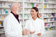 Счастливые молодые женские и старшие мужские аптекари стоя перед полками с лекарствами и говорить стоковое изображение rf