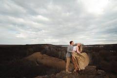 Счастливые молодые пары обнимая на краю горы, на заднем плане очень красивый ландшафт стоковое изображение