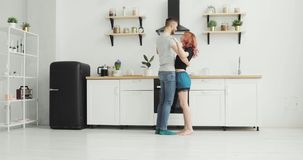 Счастливые молодые танцы пар в пижамах кухни нося слушая утро музыки дома видеоматериал