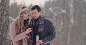 Счастливые пары держа горячие чашки чая над ландшафтом зимы Молодые пары в любов на каникулах зимы, стоя рядом с видеоматериал