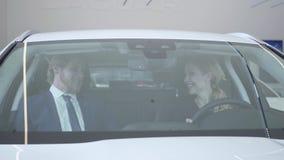 Счастливые пары сидя внутри автомобиля который они как раз купили в современном мотор-шоу Максимум 5 человека и женщины, они полн сток-видео