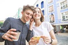 Счастливые пары слушая музыку в одном наушнике 2 Счастливый молодой человек со стеклом кофе в его руках стоковые фото