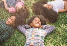 Счастливые дети ягнятся класть на траву в парке стоковая фотография rf