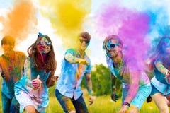 Счастливые друзья празднуя счастливый фестиваль праздника holi стоковое изображение