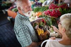 Счастливые старшие пары с корзиной на местном рынке стоковое изображение