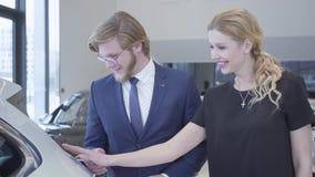 Счастливые человек и женщина между строками новых электрических автомобилей в мотор-шоу выбирая одно для покупки Пары обнимая, во акции видеоматериалы