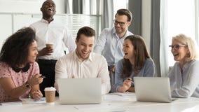 Счастливые разнообразные работники офиса объединяются в команду смеяться совместно на групповой встрече стоковые фото
