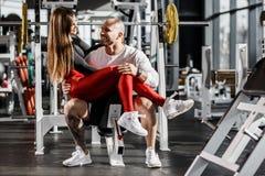 Счастливые романтичные атлетические пары Худенькая красивая девушка сидит на коленях сильного атлетического человека и обнимать в стоковое фото