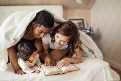 Счастливые родители читая книгу к жизнерадостному ребенку пока покрывающ с одеялом стоковые изображения