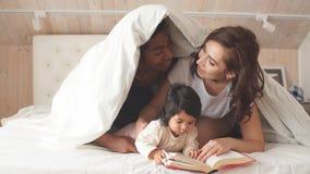 Счастливые родители читая книгу к жизнерадостному ребенку пока покрывающ с одеялом видеоматериал
