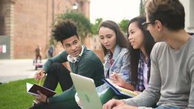 Счастливые multiracial американские друзья работают в команде после школы говоря совместно об университете и используя телефон и сток-видео