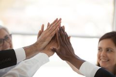 Счастливые multiracial разнообразные работники давая высоко 5 стоковые фото
