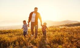 Счастливые отец и дети семьи в природе на заходе солнца стоковые изображения rf