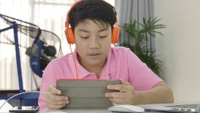 Счастливый азиатский мальчик играя на планшете с оранжевыми наушниками, акции видеоматериалы