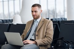 Счастливый бизнесмен работая на ноутбуке на гостиной аэропорта ждать Красивый кавказский бизнесмен на зале ожидания внутри стоковое изображение
