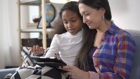 Счастливый и взрослый американский учитель женщины помогая молодому Афро-американскому студенту девушки объясняя знание и помогая видеоматериал
