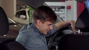 Счастливый красивый человек показывая большие пальцы руки вверх, сидящ в новом автомобиле на дилерских полномочиях сток-видео