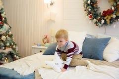 Счастливый мальчик скача на кровать Мальчик имея потеху празднуя рождество дома стоковые изображения