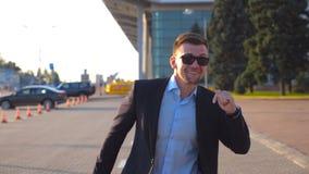 Счастливый молодой бизнесмен в танцах и петь официально черного костюма смешных пока идущ с багажом на улице города позже сток-видео