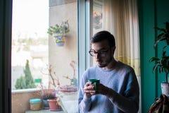 Счастливый молодой человек имея чашку кофе стоковые фотографии rf