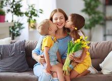 Счастливый День матери! Дети поздравляют мам и дают ей подарок и цветки стоковые изображения rf