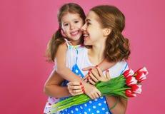Счастливый День матери! дочь ребенка дает матери букет цветков на предпосылке цвета розовой стоковая фотография