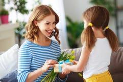 Счастливый День матери! дочь ребенка дает матери букет цветков тюльпану и подарку стоковая фотография