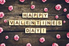 Счастливый день, надпись на деревянных кубах и бутоны Валентайн розовых роз на темной деревянной предпосылке стоковые изображения