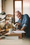 Счастливый старший мужской плотник с телефоном в мастерской стоковые изображения rf