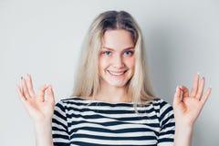 Счастливый усмехаясь красивый молодой знак ОК показа бизнес-леди с 2 руками на белых предпосылке и усмехаться Положительные эмоци стоковые фотографии rf