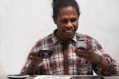 Счастливый чернокожий человек используя умный телефон дома Усмехаясь молодой африканский человек дома сидя на телефонном сообщени стоковая фотография rf