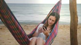 Счастливый расслабленный женский фрилансер лежа в гамаке на красивом пляже морского побережья используя усмехаться приложения пок акции видеоматериалы