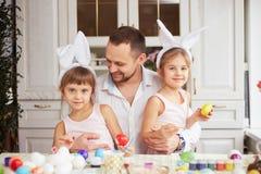 Счастливый отец и его 2 маленьких дочери с белыми ушами кролика на их головах красят яйца для таблицы пасхи внутри стоковая фотография rf