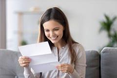 Счастливое усмехаясь письмо бумаги чтения женщины, получает хорошие новости дома стоковое изображение