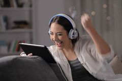 Средства массовой информации возбужденной женщины слушая и наблюдая на планшете стоковая фотография