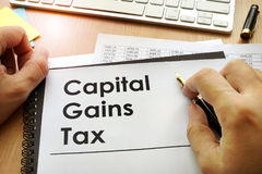 Ð¡apital gains tax CGT. Hands holding documents with title capital gains tax CGT stock image