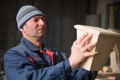 Ð¡arpenter inspecting wood furniture part royalty free stock image