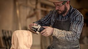 Сarpenter saw sculpture. Сarpenter, builder in work clothes saw to cut out sculpture from wooden a man`s head, using an angle grinder  in the workshop, around Royalty Free Stock Photos
