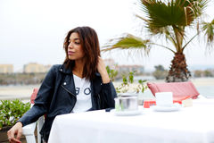 Ð¡harming female hipster sitting on the terrace of sidewalk cafe with palm tree on background stock photos