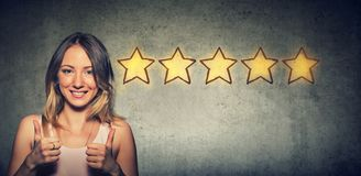 Ð¡heerful beautiful woman smiling showing thumb up like gesture choosing five stars rating. Excellent customer service concept stock photo