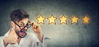 Ð¡heerful handsome man smiling showing thumb up like gesture choosing five stars rating royalty free stock photo