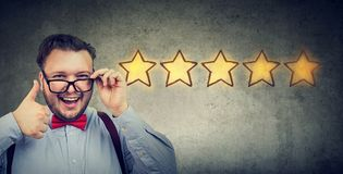 Сheerful handsome man smiling showing thumb up like gesture choosing five stars rating stock photos