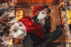 Fooling around santa. Ð¡heerful punk Santa fools around near his house with a bag of gifts in his hands stock image