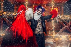 House of santa claus. Ð¡heerful punk Santa fools around near his house with a bag of gifts in his hands stock image