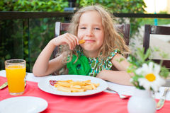 Ð¡hild eating potato chips in the cafe Stock Image