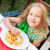 Ð¡hild eating potato chips in the cafe Royalty Free Stock Images