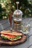 Ð¡iabatta sandwich and French press with tea. On dark wooden background stock photo