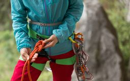 Сlimber making a eight rope knot. Сlimber wearing safety harness making a eight rope knot Royalty Free Stock Photography