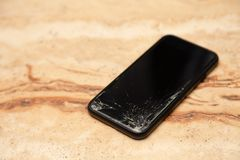 Ð¡loseup black smartphone with broken screen glass lying on wooden table. Concept of dropping phone, broken gadget, electronics. Ð¡loseup black smartphone royalty free stock images